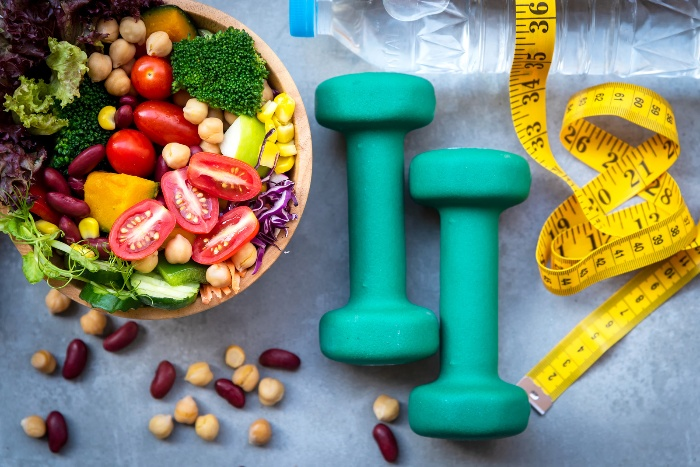 healthy meal salad nuts meter water bottle and blue weights