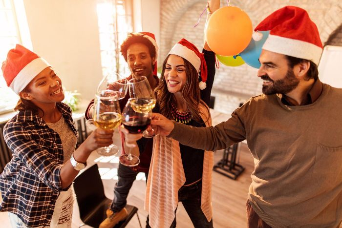 friends with santa hats raising a toast with whine glasses