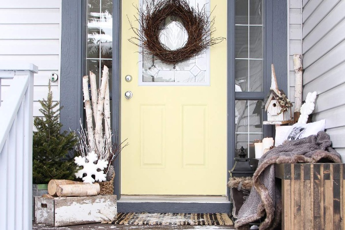 Front door and porch decor branch wreath logs and snowflake decorations