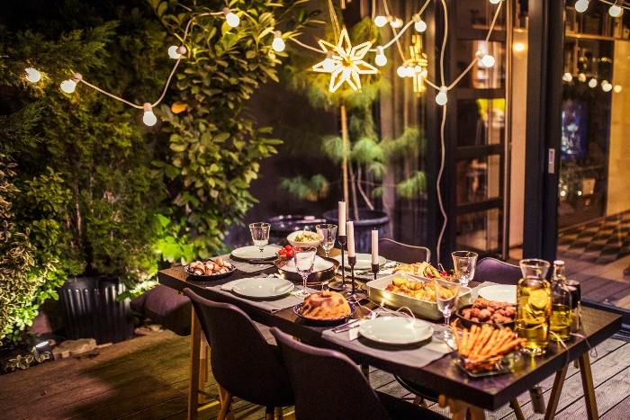 garden fairy lights over a beautiful table setting on a porch with a wooden floor