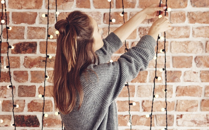 woman with long hair and gray sweater hanging fairy lights on an exposed brick wall