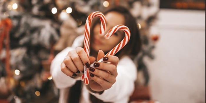 Girl in front of a christmas tree holding two white and red sticks in the shape of a heart