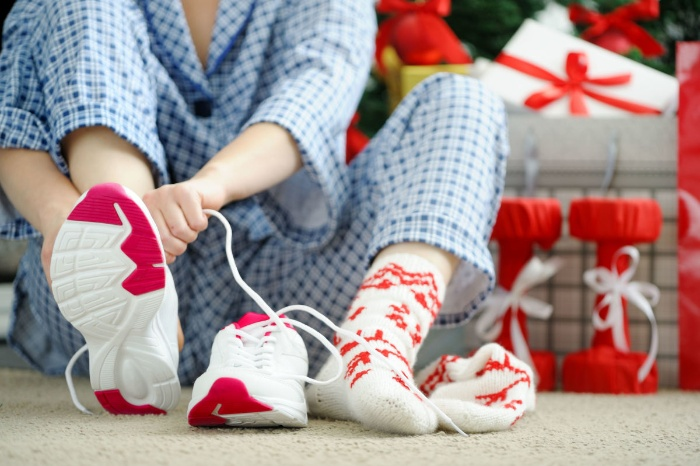 holiday fit woman in her pajamas putting her socks and sneakers on next to the christmas tree