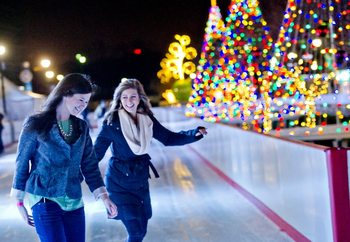 holiday fun two girls on an ice skating ring with christmas trees