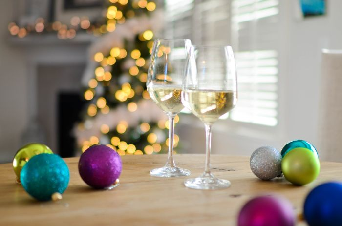 holiday glasses with white wine on a table with Christmas baubles