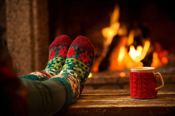 holiday relaxation feet in colorful socks in front of the fire with a mug dressed in red