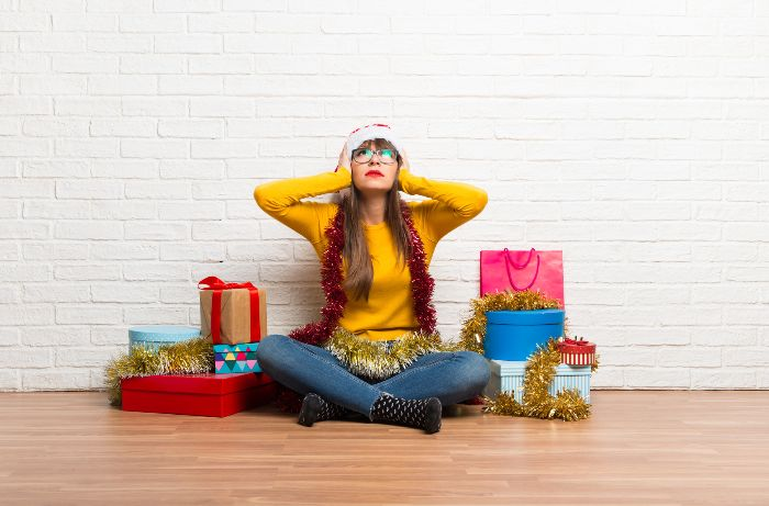 woman in yellow blouse with glasses with presents sitting on the floor with hands on her ears