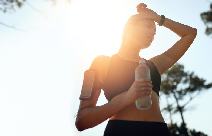 holiday workouts woman in sportwear with a bottle of water running outdoors phone on her arm