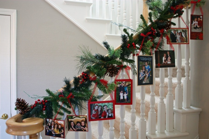 home decor staircase decorated with a green garland made of branches with hanging cards and photos