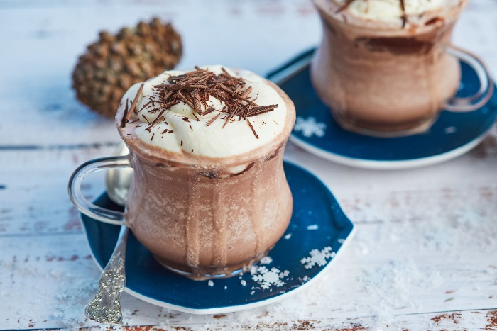 delicious hot chocolate in a glass cup on a blue plate sprinkled with chocolate