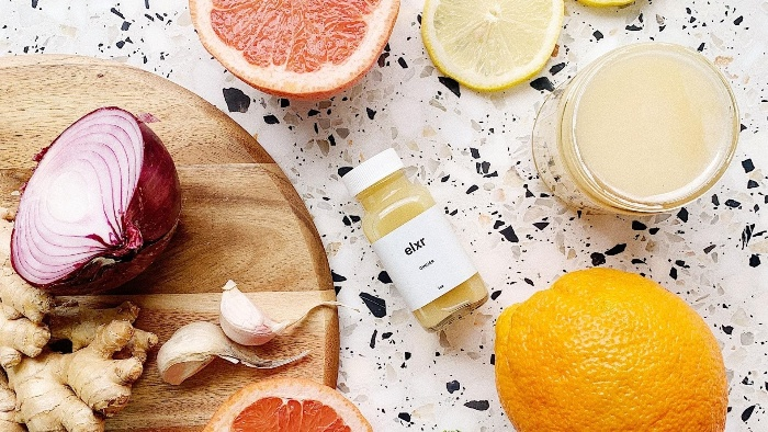 immune boosters slices of onion garlic citrus fruits on a colorful table