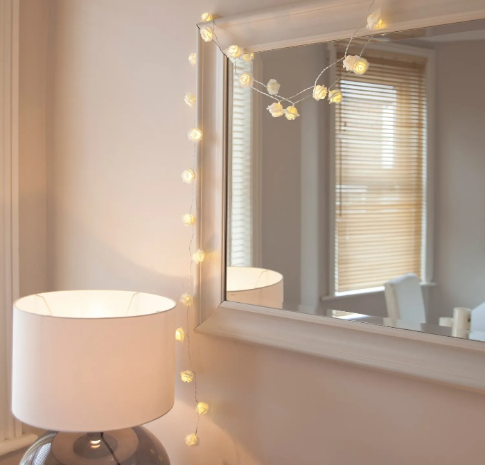 interior decor with delicate round fairy lights around a mirror