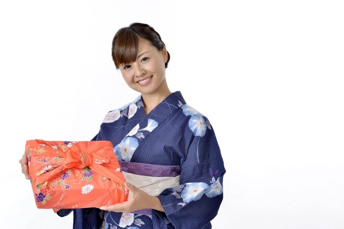 an asian woman in blue kimono holding a colorful red gift