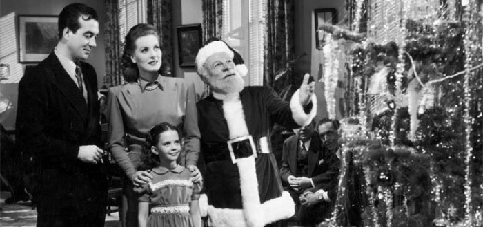 Best christmas movies a scene from a black and white christmas movie family standing in front of the christmas tree with santa claus