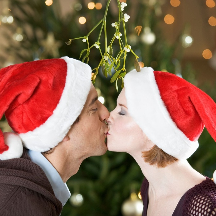 mistletoe christmas traditions a couple with christmas hats kissing under a mistletoe branch