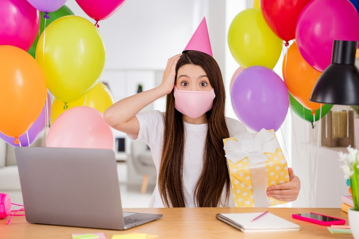 woman in front of her laptop with balloons and a present in her hand