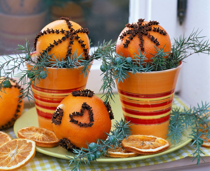 Oranges decorated with cloves on a plate with juniper