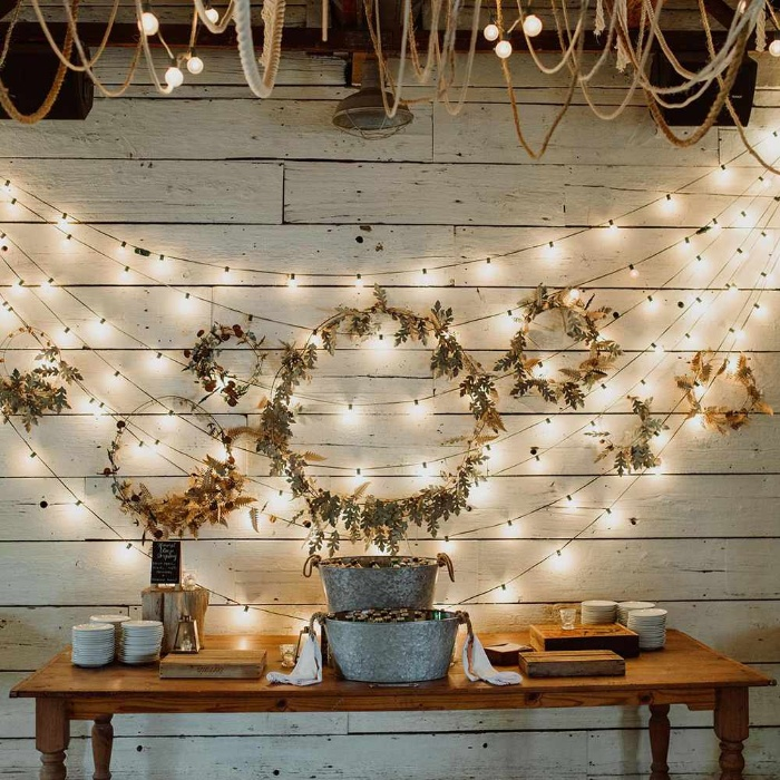 wall decor garlands of fairy lights and wreathes on a white wall above a table