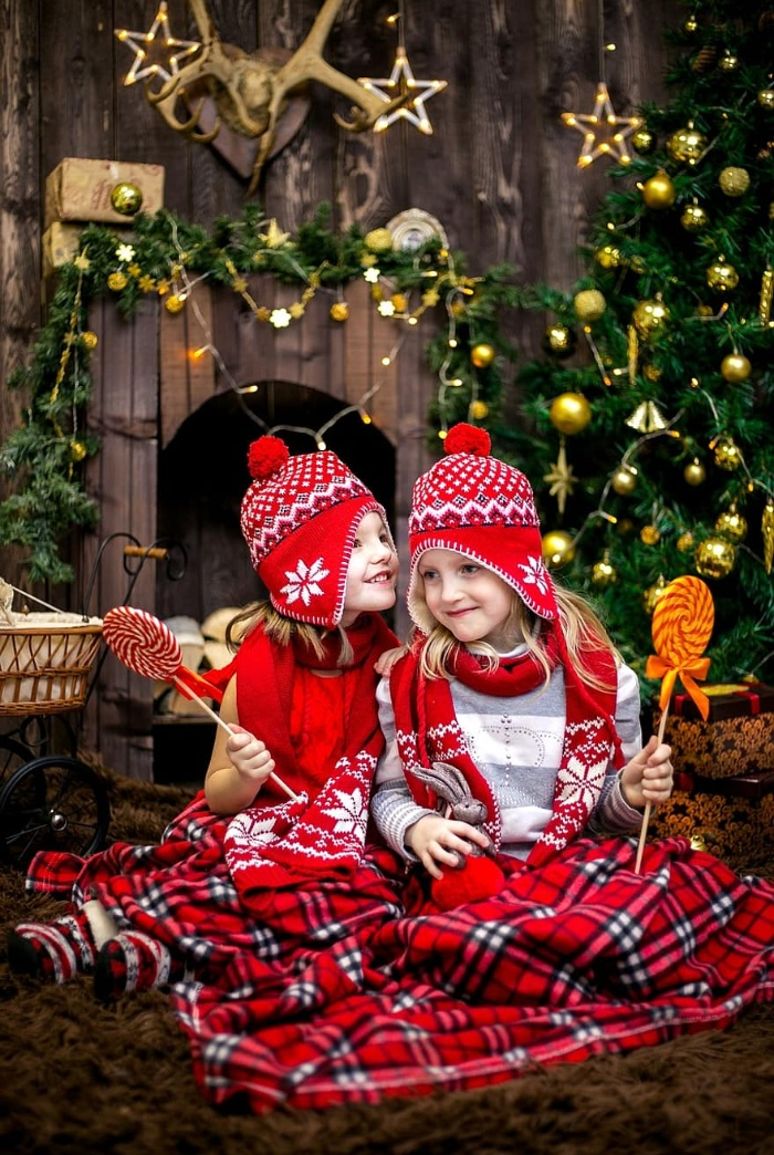 two girls dressed in a festive outfit with christmas decor in the background