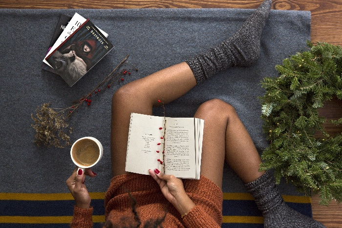 woman sitting on the floor reading a book with a coffee in her hand and holiday decor