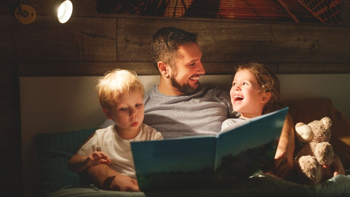 dad with two kids in bed reading a story from a book