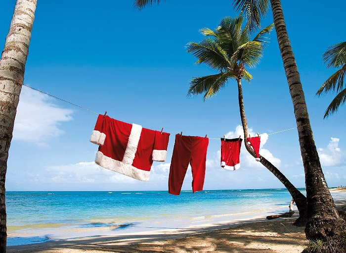 santa costume hanging between two palm trees on the beach
