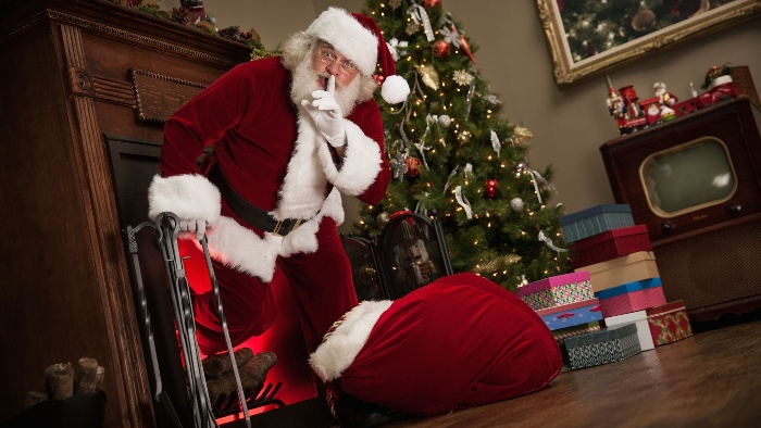 Christmas songs Santa Claus in a living room with a huge bag of gifts