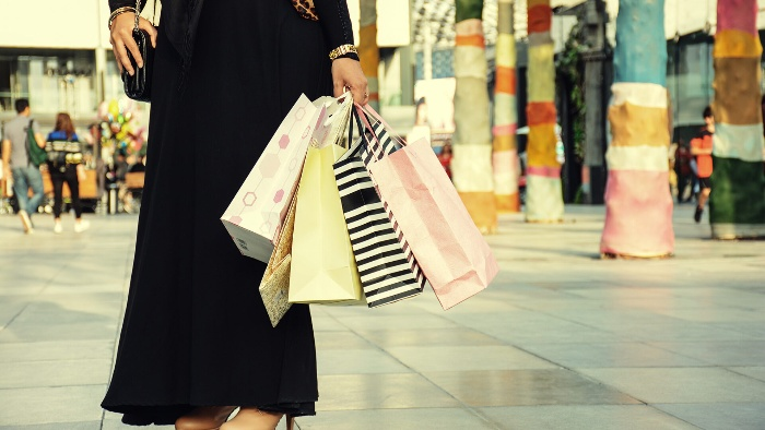 shopping in saudi arabia woman in a black burka holding colorful paper bags with gifts