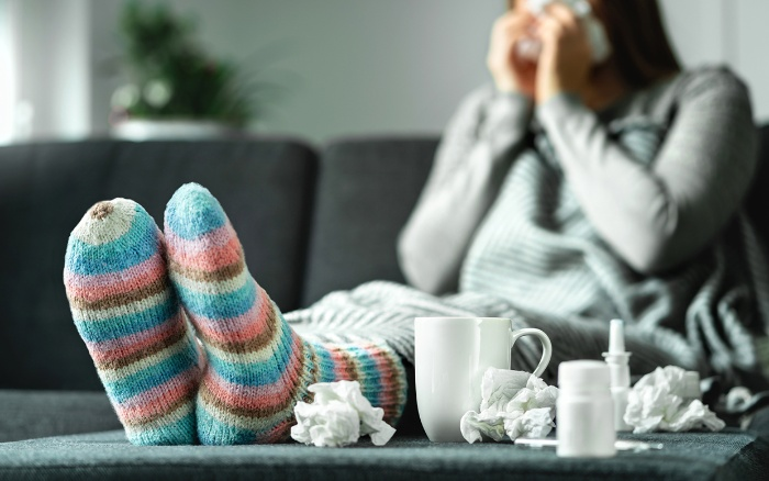woman with socks sitting at home on the sofa sneezing flu season paper tissue