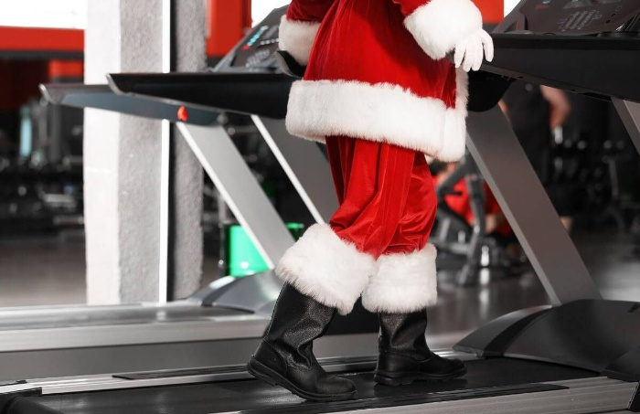 stay active during the holidays santa in a fitness room exercising