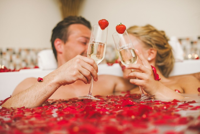 taking a bath together couple taking a bath full of rose petals with glasses decorated with strawberries