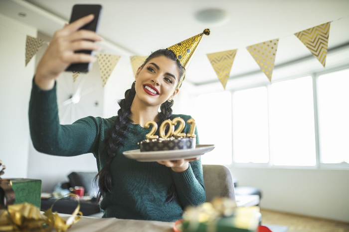 woman with a party hat holding a cake with 2021 sign and taking a selfie