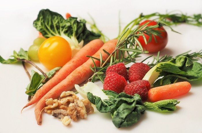 vegetables on a table carrot strawberries greens rosemary walnuts tomatos
