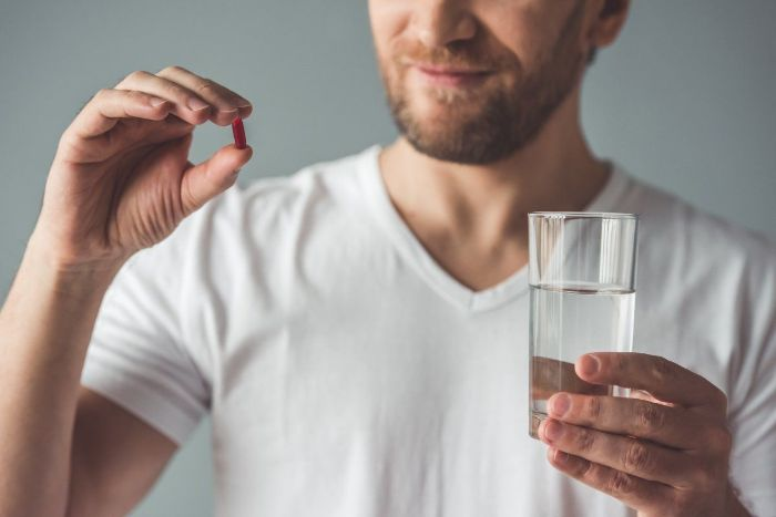 Man in white shirt with a beard holding a glass of water and a vitamin pill