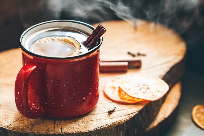 Hot tea with citrus slices and cinnamon sticks on a natural wooden surface