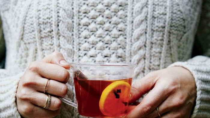 woman dressed in sweater holding a glass cup with warm tea cinnamon stick and orange peel