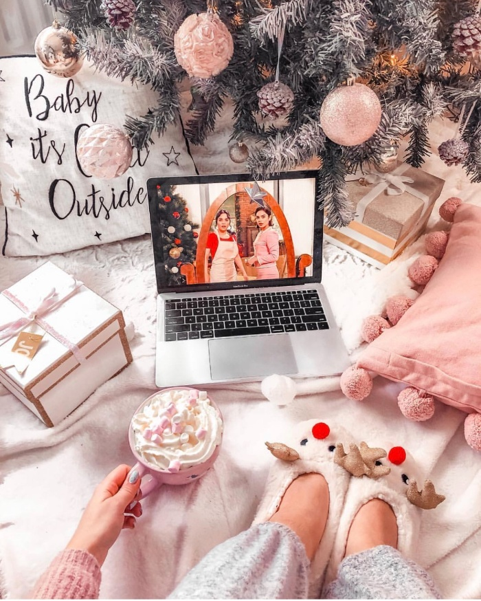 girl with a laptop under the christmas tree with deer slippers pink tree decor and pillows