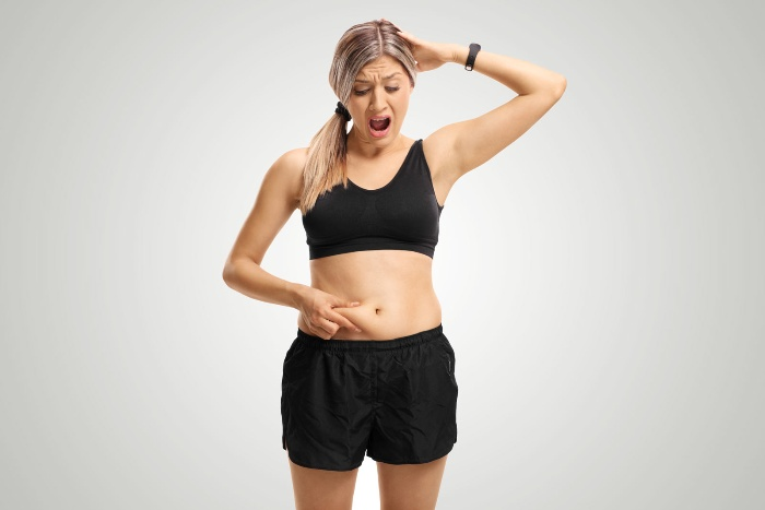 woman dressed in black showing her belly fat