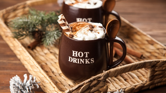 winter coffee in brown mugs with cream on top in a tray