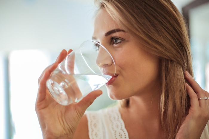 blond woman dressed in white drinking water from a glass cup