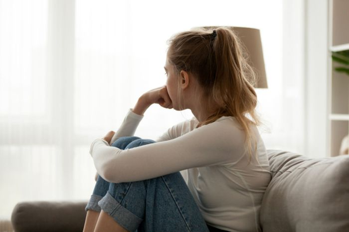 woman sitting on the sofa dressed in jeans with her legs up looking through the window