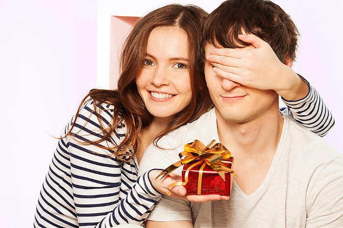 woman in striped shirt giving a man a little gift covering his eyes with her hand
