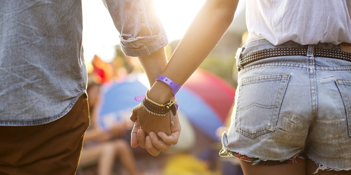 girl and boy holding hands at a festival