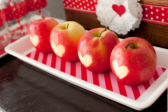 apples on a white tray with hearts carved in them
