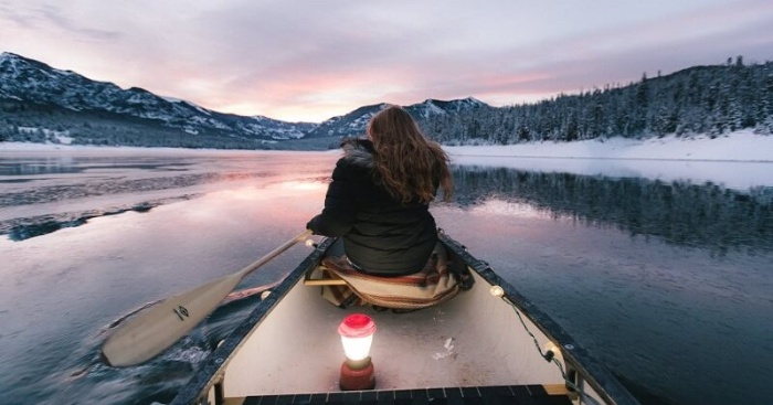 woman in a boat rowing among a snowy landscape