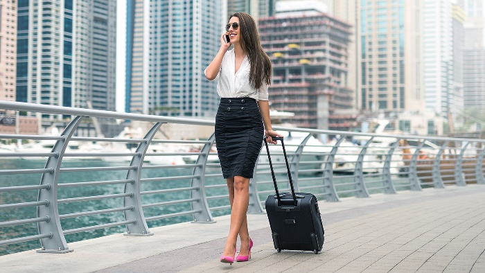 businesswoman in a black skirt and white shirt walking with her suitcase in a business district