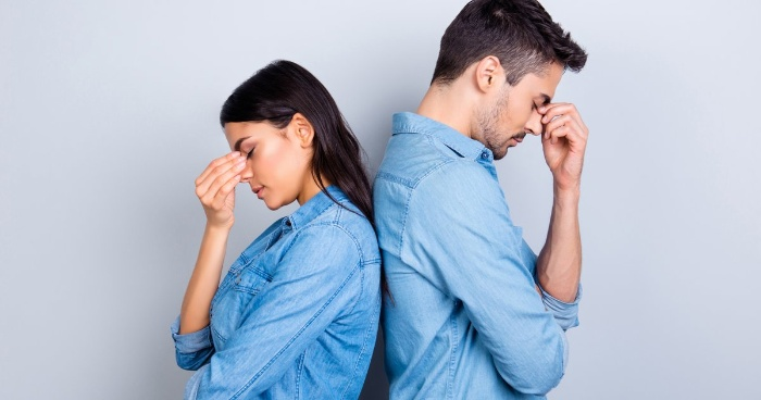 woman and man in denim shirt holding their heads back to back