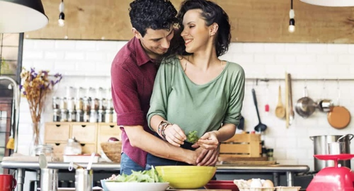 couple hugging and cooking together in a kitchen