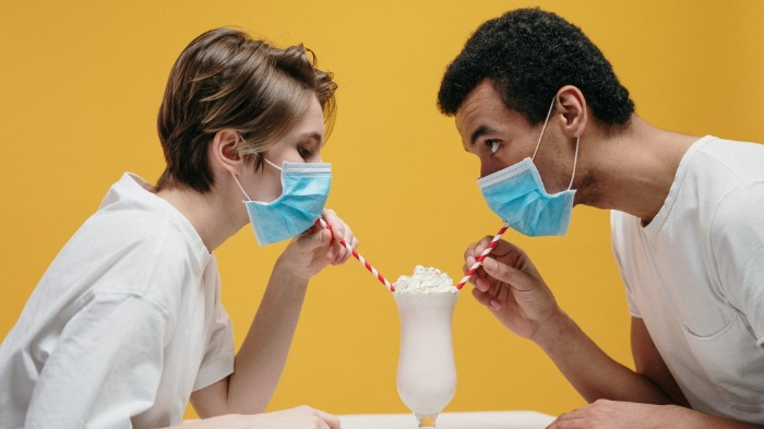 couple with masks on a yellow background drinking shake from two straws