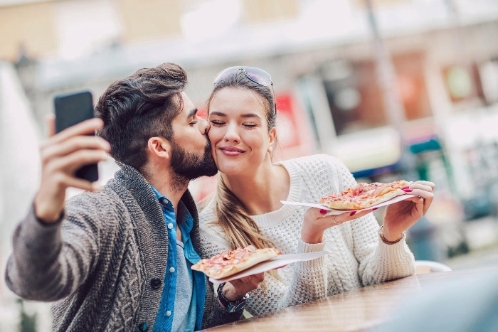 a couple eating pizza outside man taking a selfie with his phone
